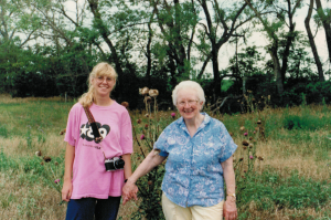 Kristin and our grandmother posing in front of musk thistle, a noxious weed in Nebraska